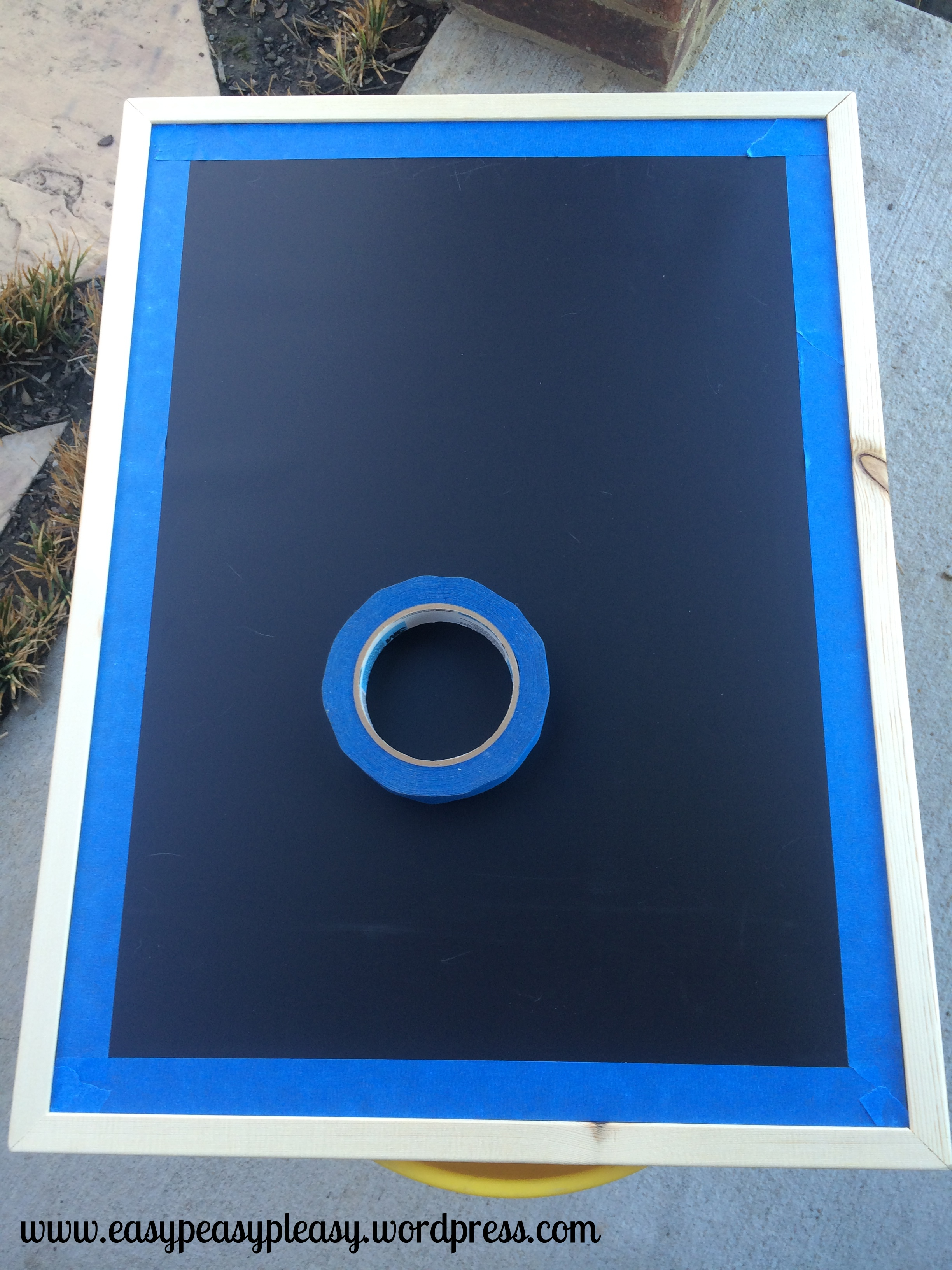 Using painters tape to paint chalkboard frame to tell people you are pregnant