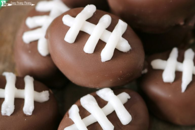 Easy game day snack idea. Take the traditional chocolate covered peanut butter balls to the next level with these Peanut Butter Footballs.