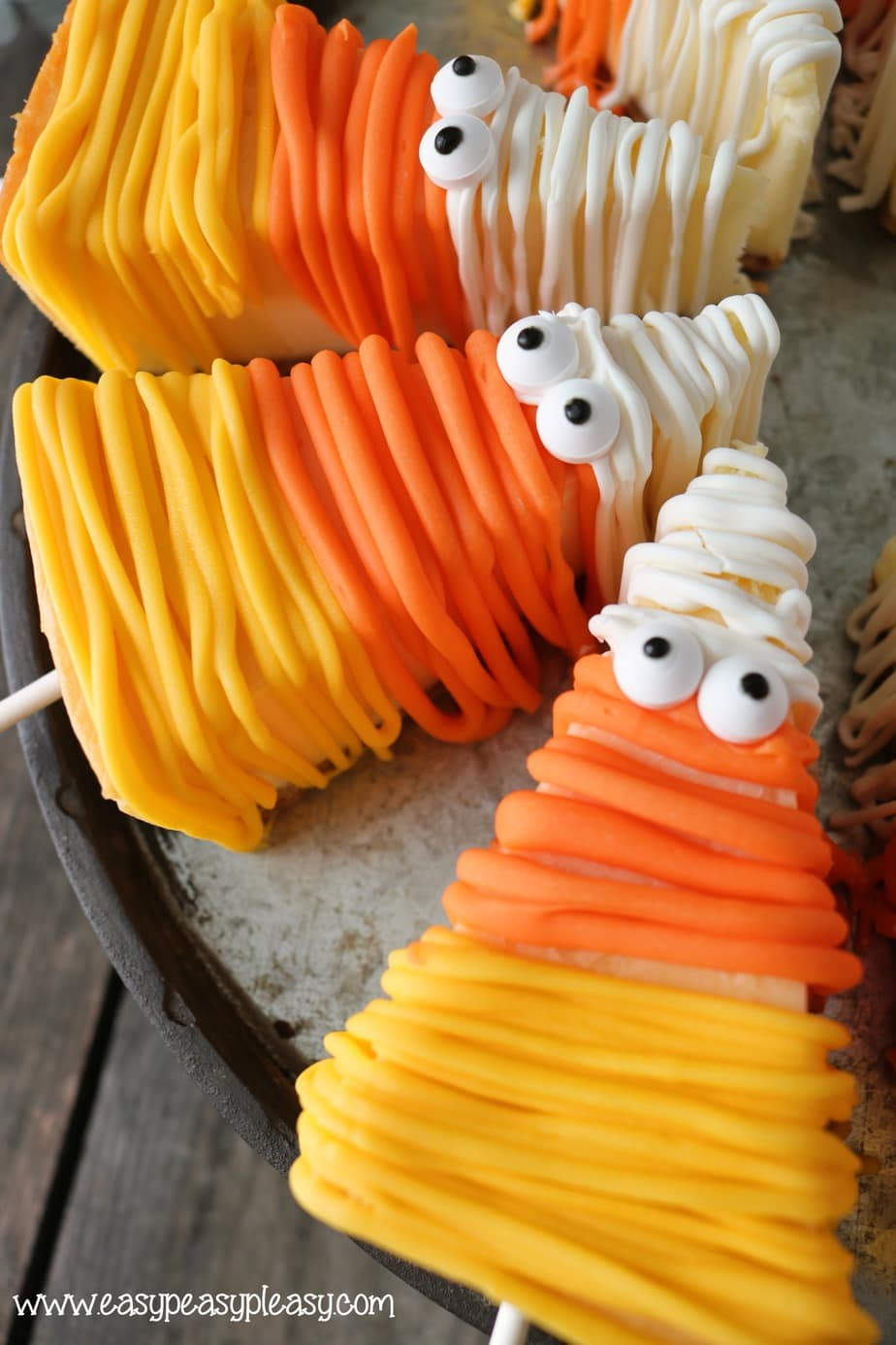 Mummified Candy Corn Cheesecake on a Stick at easypeasypleasy.com
